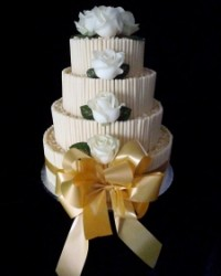 white chocolate scrolls and curls wedding cake with bow and ivory roses