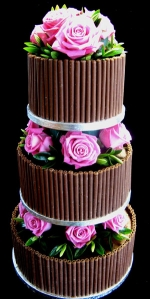 milk chocolate wedding cake with pink roses and chocolate curls